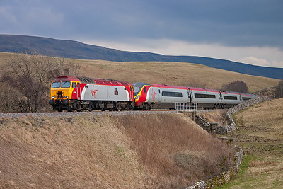 Northbound trains appear with very little warning, 57316 drags 390026 under threatening skies. This diverted train is 1C56 1117 Euston to Carlisle.