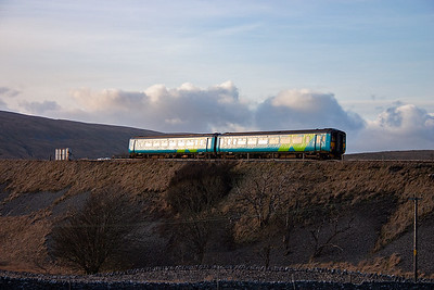 The sun glints off the unit as it heads north. It will pass over the Ribblehead viaduct in a few hundred yards.