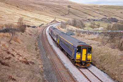 153358 and 156469 climb hard against the 1 in 100 pull over new track and ballast at the overbridge which once marked the county boundary between Cumberland and the North Riding of Yorkshire. The working is 2H89 1149 Carlisle to Leeds.