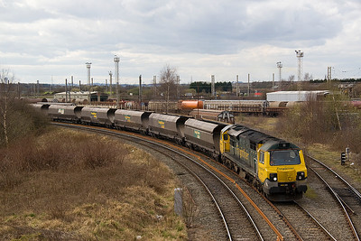 The sun hasgone as 70002 brings 6F02 from Ellesmer Port to Fiddlers Ferry past Arperly yard.  19/03/11
