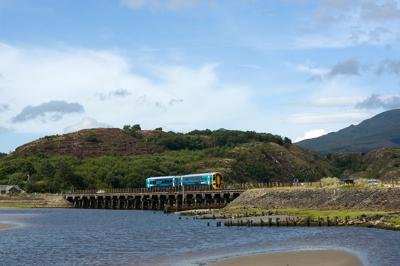The old woodedn bridge at Penrhyndeudraeth is due for replacement - here 158840  crosses with the 1537 Pwllheli to  Macynlleth.  The cars are on the adjacent road which shares the bridge. 2/8/12