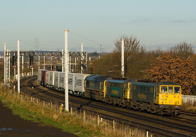 Unusual these days to see class 86s in the daylight round Warrington.  86639 and 86610 are dragging dead 66541 and the short 4M27 Coatbridge to Crewe  past Winwick- 01/12/12.   I don't think of the 66s as large locos, but the 66 certainly looks much bulkier than the 86s