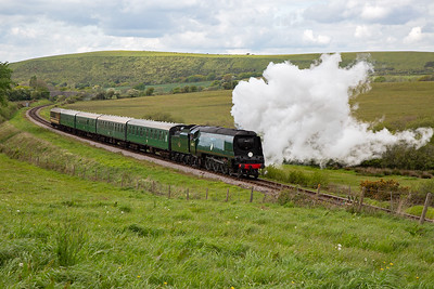 The weather conditions are such that the exhaust is pure white and lingers as the wind blows it over the side of the loco.