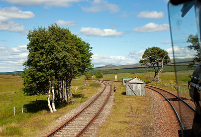 The loop is on a sweeping left hand curve when heading north. Between the two huts is the short earth platform that housed a coach body which formed a school in the 1930's.