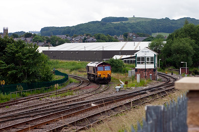 66025 gains the road with its wagons and passes behind Buxton's signal box.