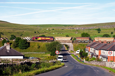 The train passes over the road from Harpur Hill to the main road at Heathfield Nook. In the background is evidence of quarrying and the railway embankment that served it.