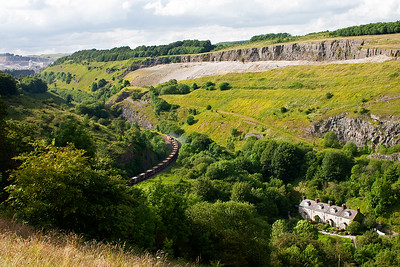 A stunning view of Chee Dale and the former Midland Railway signallers cottages at Blackwell Mill. A triangle of lines was once here with the former Midland Railway route to Derby and London running off to the right through Chee Dale and onto Monsal Gorge. 66025 runs along the remaining side of the triangle with its train of loaded stone boxes. Below is a link to a view taken in 1963  https://www.geograph.org.uk/photo/3388155