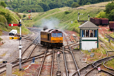 60047 has left its wagons for reloading and now leaves the quarry access road and crosses onto the up goods road and passes the former Midland Railway signalbox and will stable in the yard behind it.