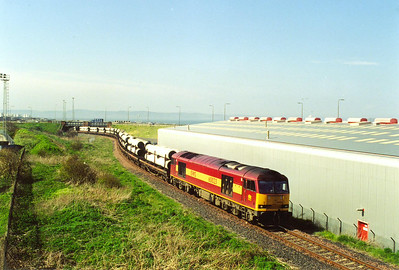 60023 slowly traverses the Leith Docks branch with its pipes for the south.  The train is bound for Wansford on the private Nene Valley Railway and is part of a new gas pipeline.  At one time, the area now occupied by the large shed was a mass of sidings.