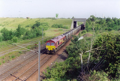 An arrival at Millerhill passes below the A1 with 66044 in charge of 7B64 0630 from Falkland Yard to Cockenzie power station loaded MGR.
