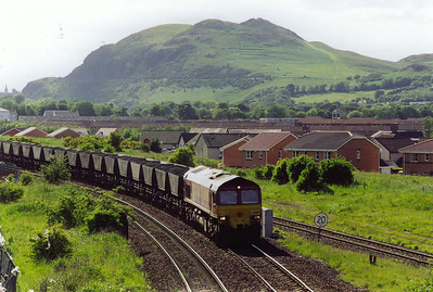 The southern flank of Arthur's Seat provides a dramatic backdrop of 66087 and its rake of loaded HAA hoppers. The train is 6U26 1554 FX Mossend to Eggborough Power Station. The single line leads off to Portobello Junction on the ECML.