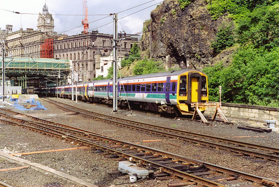 "Four class 158 units sit in the warm summer sun between duties. The former North British Hotel forms the backdrop, it is now called ""The Balmoral""."