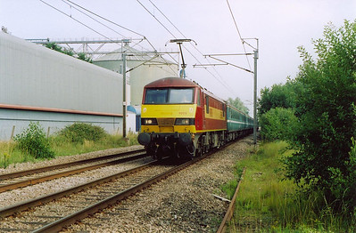 EWS liveried 90018 fronts the 1000 off Norwich to Ipswich. The level crossing is at Sneath Common.