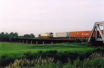 The lowering evening sun glints off DRS 66407 on hire to Freightliner for the duration of the diversions. The train is 4E50 1845 Ipswich Yard to Leeds diverted Freightliner. The train is crossing the 100 foot Washes near Pymoor on the line to March and  Peterborough.