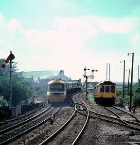 An IC 125 climbs away from Par towards Penzance , passing the Newquay branch DMU stabled in the headshunt 5/9/85