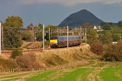 A northbound GNER working to Glasgow Central comes sweeping round the bend by Spittal with 91127 leading 1S13 1100 off Kings Cross.  The scene here is in full sun whilst Berwick Law is in deep shadow.