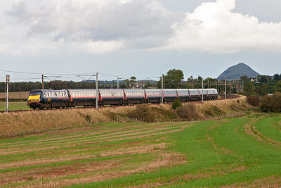 GNER 91114 propels its train south at Spittal with Berwick Law rising 614 feet  dominating the scene.  The train is 1E19 1500 Edinburgh to Kings Cross.
