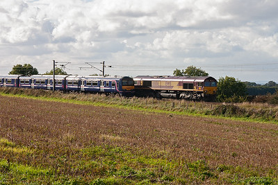 The set passes a southbound freight hauled by 66186.