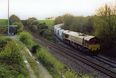 Down at Burngullow and 66090 eases itself and its loaded rake of CDA hoppers off the Parkandillack branch as 6C82 1945 to Lostwithiel.  The ivy clad building between the two lines is the remains of the Cornwall Railway station that closed on 14/9/1931.  The singled main line has since been redoubled back due to increased traffic.  17/4/2002