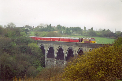 In wet conditions 67004 crosses Gover Viaduct, over the Gover Valley, to the west of St Austell, with 5C02 0859 Penzance to St Blazey empty TPO.  The line drops at 1 in 90 in the up direction.  17/4/2002