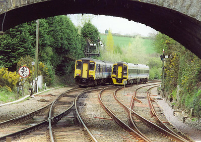A pair of sprinter units pass just beyond and framed by the road over bridge at Par station. 150248 is working the 1333 Penzance to Liskeard all stations with 158830 going in the opposite direction running empty stock.  14/4/2002