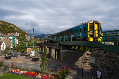 158832 with the 15:37 Pwllheli to Machynlleth service makes it's way along the concrete railway bridge that runs alongside the harbour.