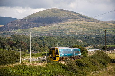 158841 with the 12:08 Birmingham International to Pwllheli service approaching Llandanwg station, with the Cambrian Mountains in the distance.