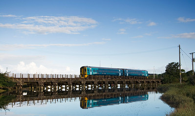 158825 with the 07:20 Pwllheli to Birmingham International service crossing the River Arfon.