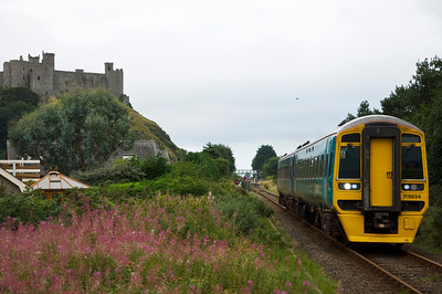 158834 pulls away from Harlech station with the 08:57 Machynlleth to Pwllheli service. Harlech Castle dominates the skyline.