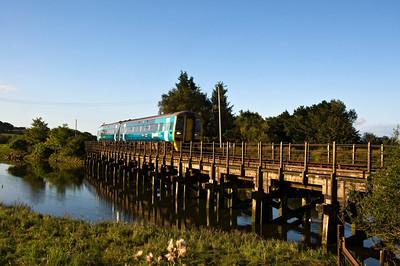 the 06:47 Machynlleth to Pwllheli service crossing the RiverArfon.