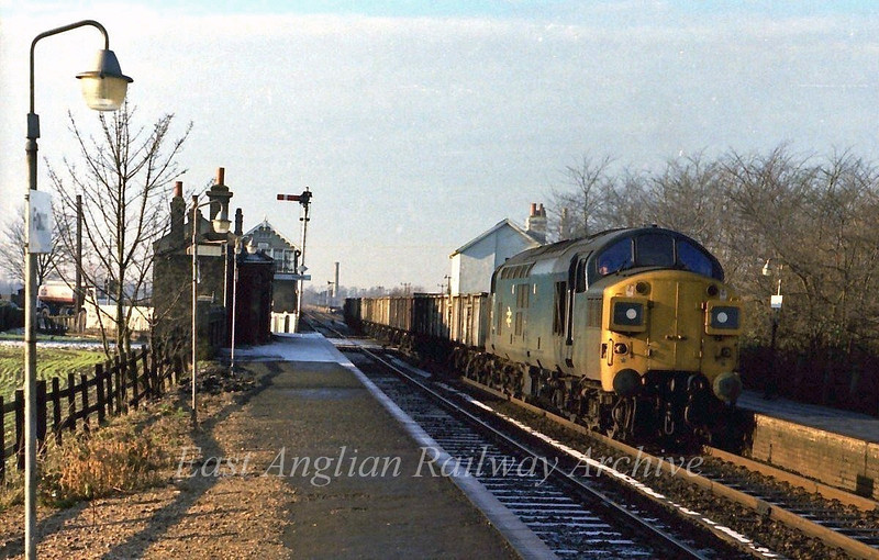 37036 hauls a freight out of Barrington Cement Works Siding at Foxton. 21st January 1978