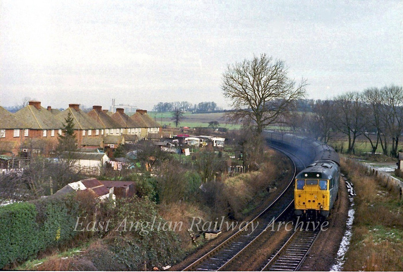 31407 accelerates away from Shepreth Branch Junction at Great Shelford with the 1130 Cambridge to Kings Cross on 21st January 1978. Two weeks later, through hauled services  to Kings Cross ceased. The chimneys of Addenbrookes Hospital can be seen on the skyline.