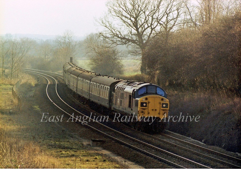 37022 passes through the Cambridgeshire countryside near Great Shelford with the 1450 Liverpool Street to Kings Lynn on 23rd February 1980. The track bed of the Stour Valley line to Sudbury and Colchester which left the main line here can be seen to the left.