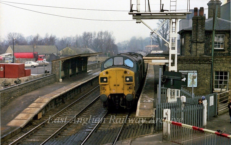 With a few remaining traces of snow on the ground 37110 roars through Shelford with the 1026 Cambridge to Liverpool Street on 18th February 1978. Shot taken from the signal box door. Sadly a vantage point no longer available.