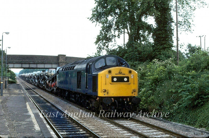 A train load of new Ford imports pass through Kennet on 25th June 1980 with 40197 in charge. The working is the 1425 Parkeston to Bathgate/Mossend (Glasgow)