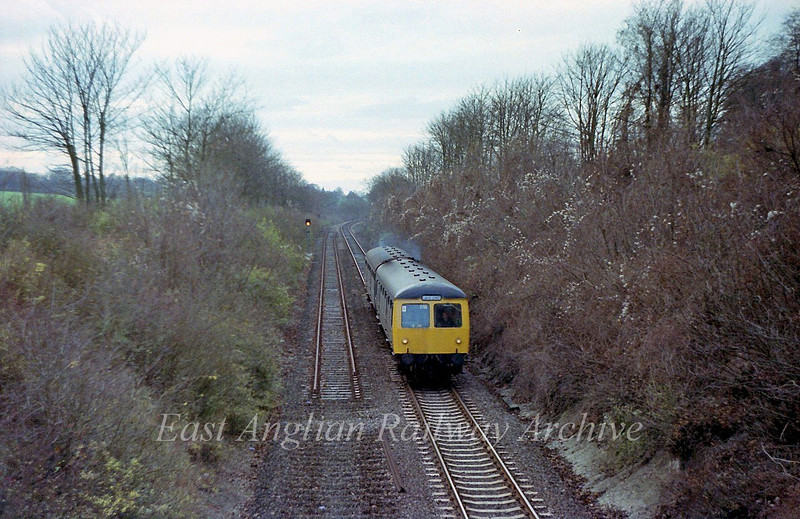 North east of Dullingham is the bridge carrying the road to Stetchworth. An Ipswich bound dmu is approaching the bridge. The line has just been made single with the Up line truncated at this point. To the left is Dullingham's Up distant.  8th December 1979.