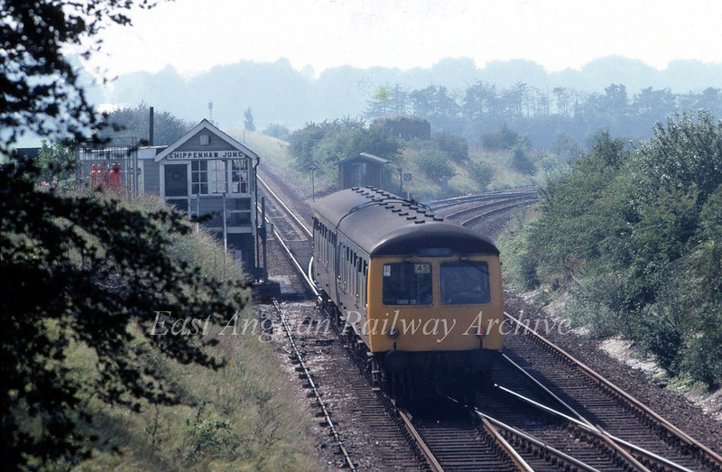With heat haze in the background the 1250 Ipswich to Cambridge heads on to the single line to Warren Hill Tunnel and Newmarket at Chippenham Junction. 27th August 1980