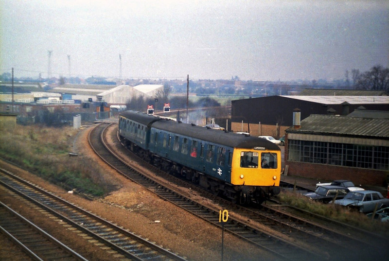 A Cravens unit forming an Ipswich to Cambridge working nears the end of its journey at Coldhams Lane Junction, Cambridge. c1979. The floodlights of the Cambridge United Football Ground on Newmarket Road can be seen in the background.