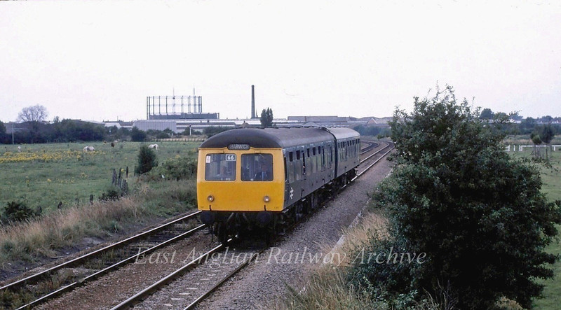 Two car Cravens  crosses Coldhams Common, Cambridge on a Cambridge to Harwich working in September 1980 with driver Cliff Fenn. On the skyline is the gasometer and the pumping station chimney off Newmarket Road. The latter as seen on TV when steeplejack Fred Dibnah climbed it.