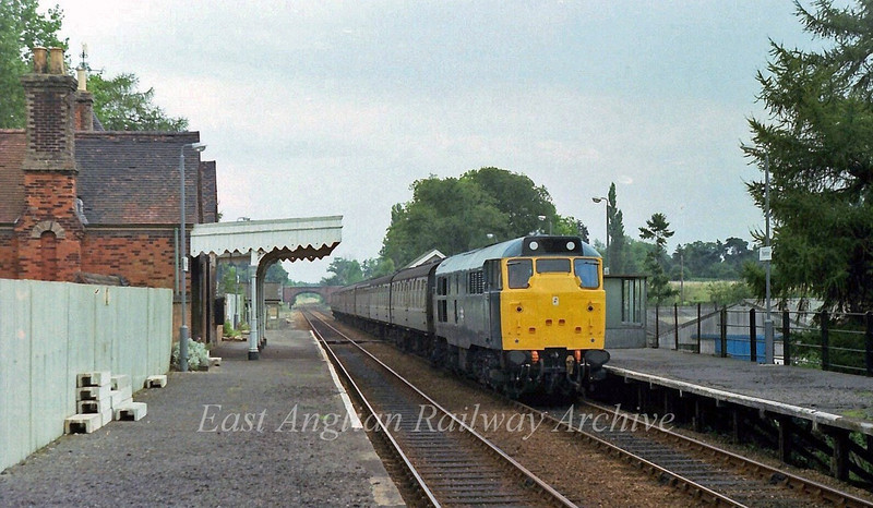 The 1240 Parkeston Quay to Peterborough working in the seventies was nealy always loco hauled. 31177 is seen here speeding through Thurston on  29th August 1978