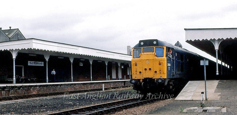 31124 waits the right away at Bury St Edmunds with the 1240 Parkeston Quay to Peterborough.  1st August 1981