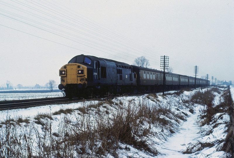 The Winter of 1981/1982 produced heavy snow falls. 37092 heads across the Fens between Cambridge and Waterbeach on a Liverpool Street to Kings Lynn working in February 1982. Milton Crossing house can be seen in the distance.