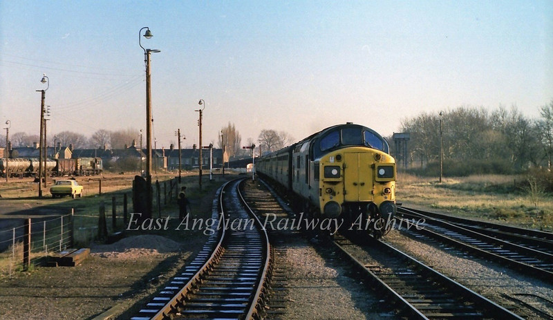 37017 arrives at it's destination with the 1036 Liverpool Street to Kings Lynn on the last day of 1979. An 08 shunts wagons in the goods yard.