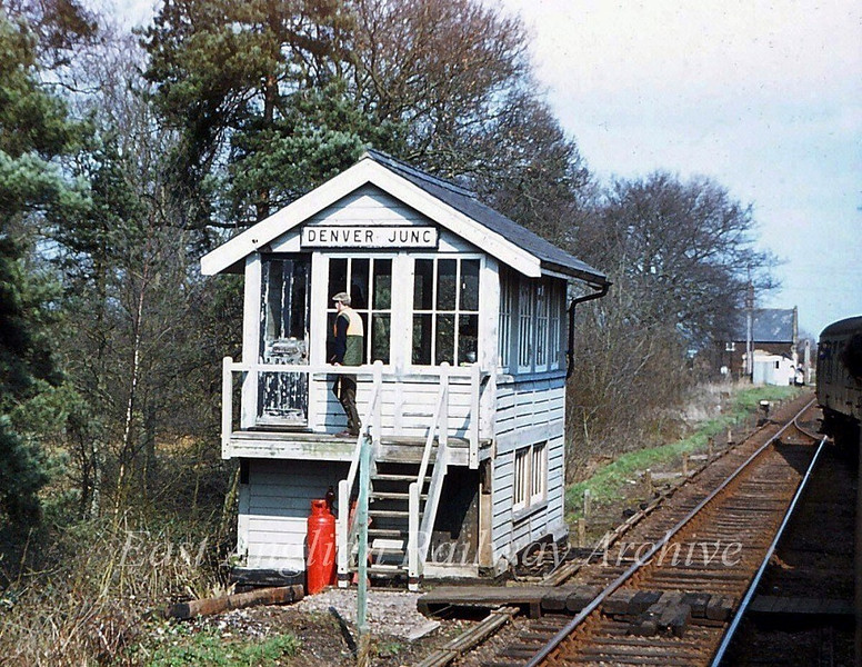 Denver Junction Signal Box on 29th March 1980. The signalman is returning to the box with the staff for the single line to Abbey. The picture is taken from the West Norfolk Freightline Railtour which has just rejoined the main line from Abbey. Denver was the junction for the Stoke Ferry Branch.