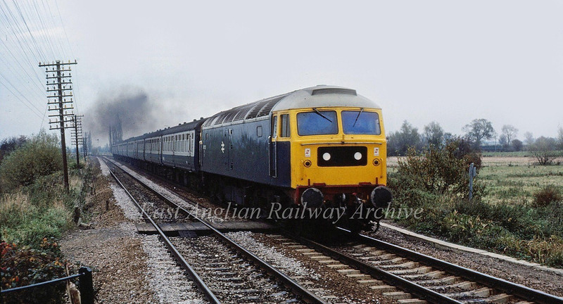 An unknown Class 47 rushes south at Waterbeach with a KIngs Lynn to Liverpool Street working in August 1981.