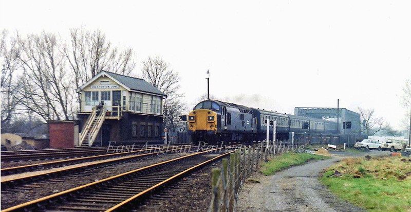 A scene now a distant memory. 37035 races past Chesterton Junction Signal Box with the 0836 Liverpool Street to Kings Lynn on 7th May 1979. The line to St Ives is in the foreground. The tarmac track used to lead to two railway cottages located in the apex of the junction.which were long gone when the photo was taken. The area to the right is now residential.