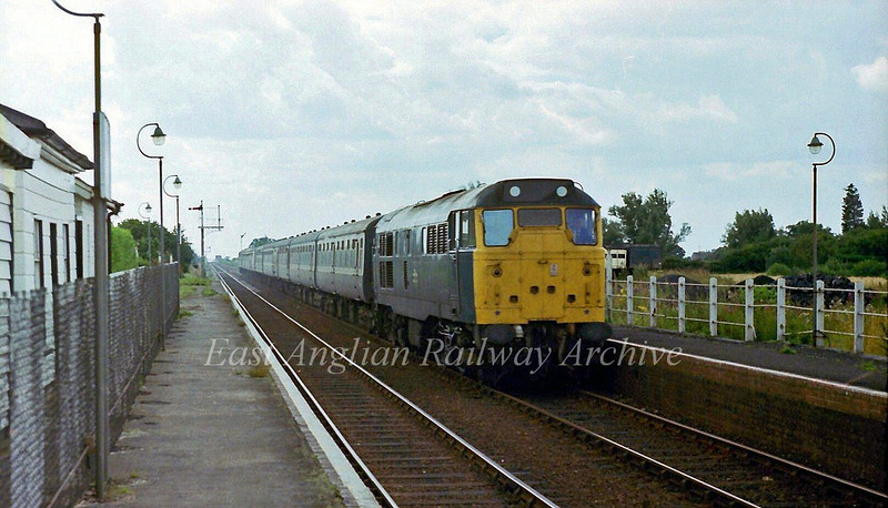 Magdalen Road on 16th August 1978. 31197 is passing on the 0836 from Liverpool Street. In the background is the redundant signal arm for the line to Wisbech.