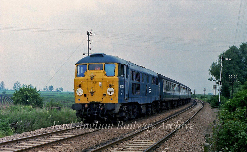 31105 heads the 1130  Kings Lynn to Liverpool Street near Queen Adelaide between Ely and Littleport. Single line working is in force after a Middleton Towers to Doncaster freight had ripped up the up line at Littleport the previous evening.  9th June 1979