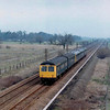 The view north from the A14 bridge with the 1103 Norwich to Cambridge approaching. Milton Crossing cottage can be seen in  the distance. The shot was achieved  by parking up on the bridge. These days it would be rather dangerous with the vastly increased volume of traffic.  Image dated 1st April 1979.