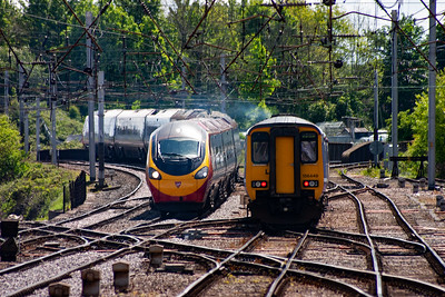 156448 smokes its way out of the station on the Maryport line with 2C30 1247 Carlisle to Barrow In Furness. Beside it 390010 slides smoothly and cleanly towards the station working 1S48 0930 Euston to Glasgow Central.